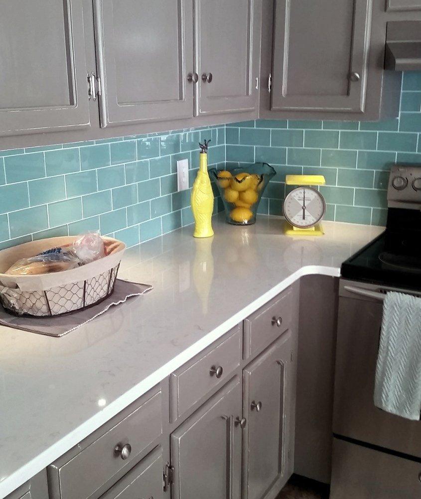 Tablier turquoise et meubles gris dans la cuisine