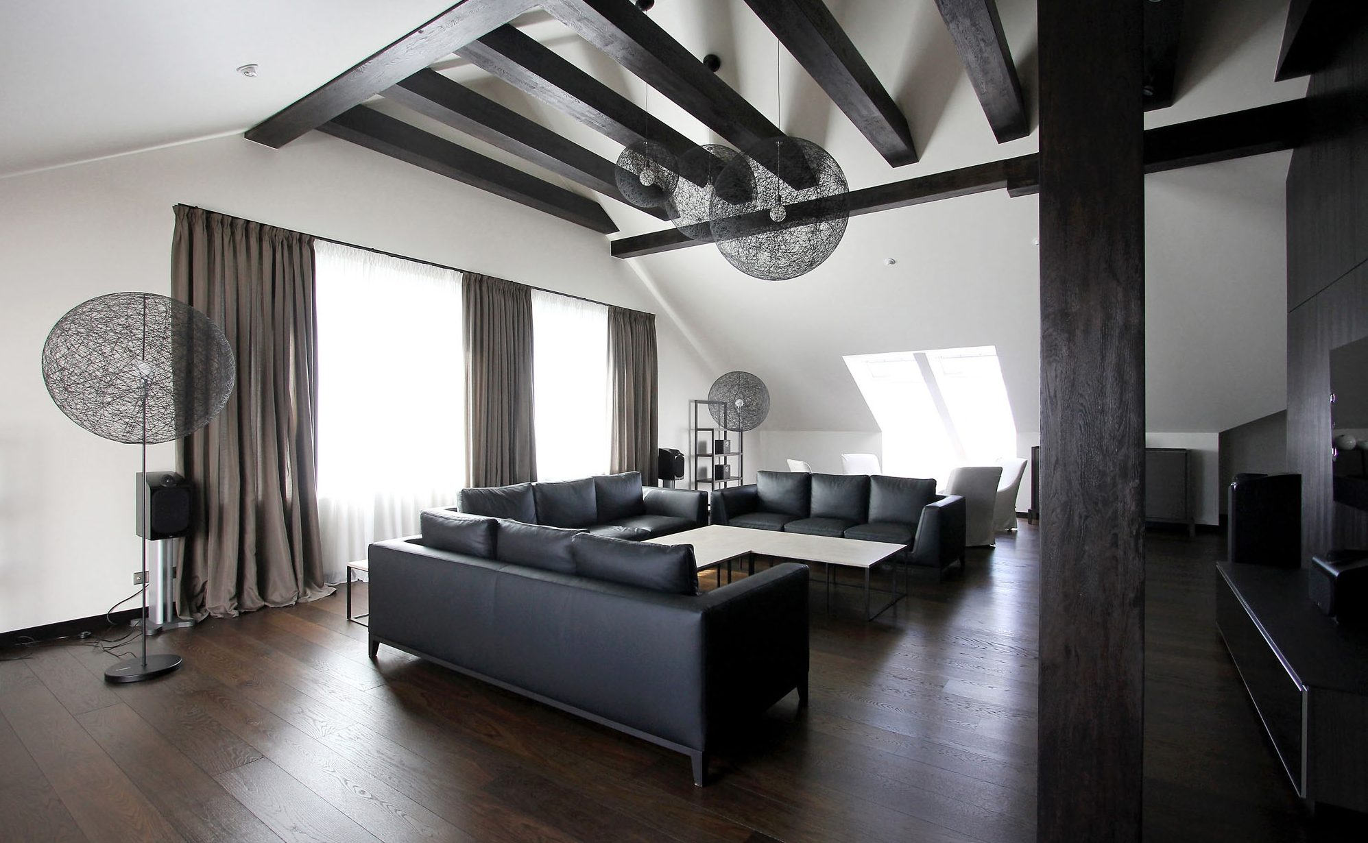 Black beams on the ceiling in the living room interior