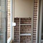 Garderobe med rulleskodder på en mursteinloggia