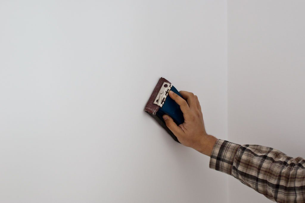 Ponçage des murs après le masticage